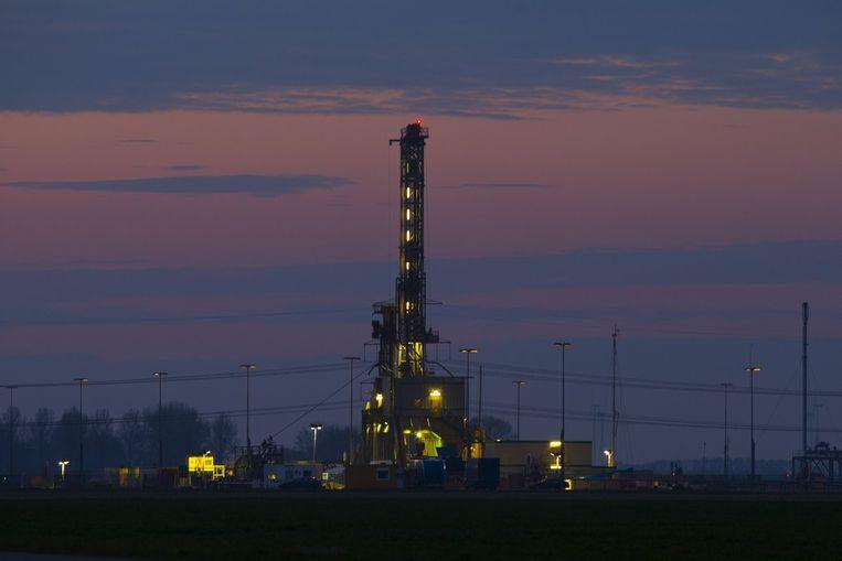 Een verlichte boortoren van de NAM bij avondlicht op een productielocatie voor aardgas nabij het dorp 't Zandt. Beeld anp
