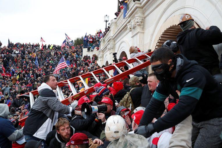 Betogers proberen het Capitool binnen te dringen aan de noordkant van het gebouw.  Beeld REUTERS