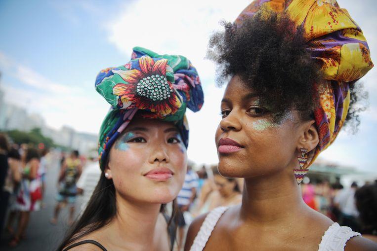 Twee vrouwen nemen deel aan een optocht voor gendergelijkheid in Rio de Janeiro op International Women's Day, 8 maart. Beeld Getty Images