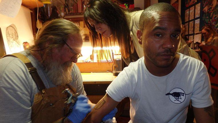 Serrio (r) krijgt een tattoo van Henk Schiffmacher. Zijn vrouw Louise Schiffmacher ziet dat het goed is. Beeld Schuim