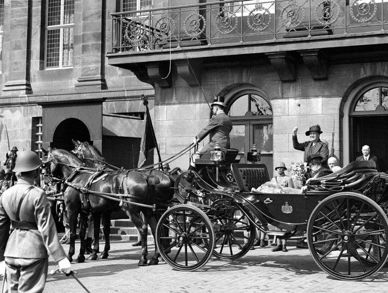 Tijdens een bezoek aan Amsterdam zwaait koningin Wilhelmina het publiek toe, juni 1937. Beeld anp