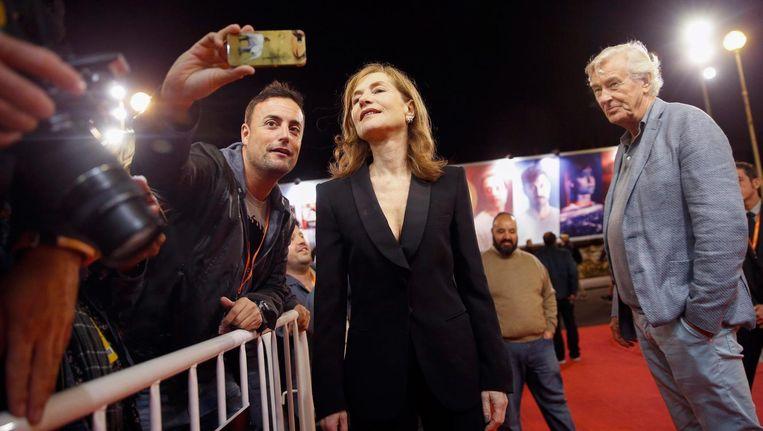 Een fan neemt een foto met actrice Isabelle Huppert, rechts regisseur Paul Verhoeven, voor de vertoning van Elle op het filmfestival van San Sebastian. Beeld epa