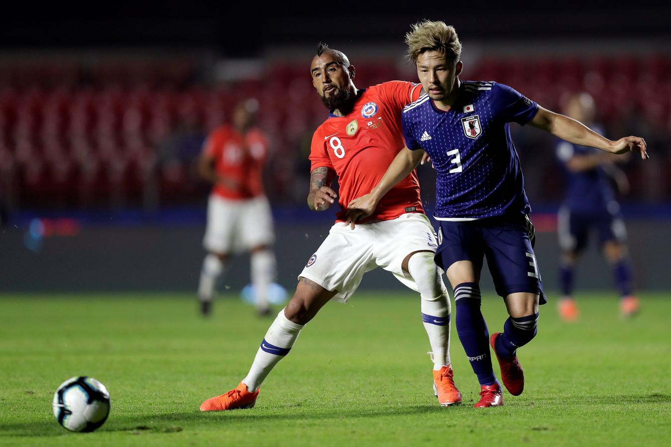 Yuta Nakayama (r) in duel met Arturo Vidal van Chili.
