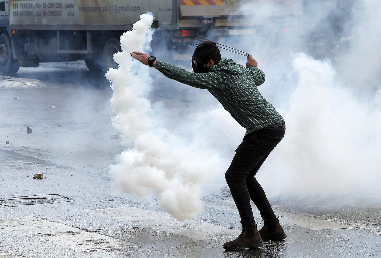 Een Palestijnse demonstrant probeert een traangasgranaat terug te gooien tijdens rellen op de Westelijke Jordaanoever. Beeld AFP