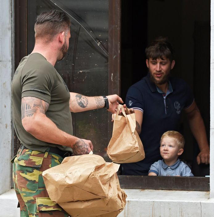 Een soldaat brengt eten naar een getroffen gezin in Pepinster.