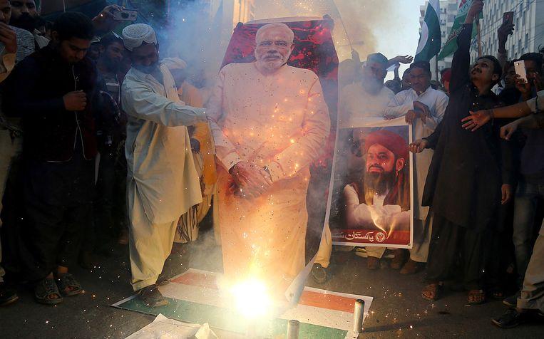 In Pakistan werden posters van de Indiase president Modi verbrand om het neerhalen van Indiase straaljagers te vieren  Beeld EPA