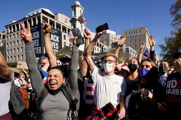Aanhangers van Joe Biden vieren feest op het Black Lives Matter Plaza in Washington. Beeld AP