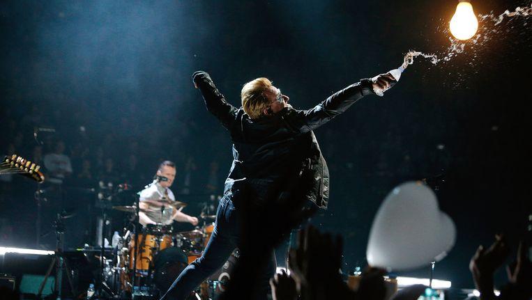 U2-voorman Bono gooit water over bezoekers van een concert van de band in Parijs. Beeld ap