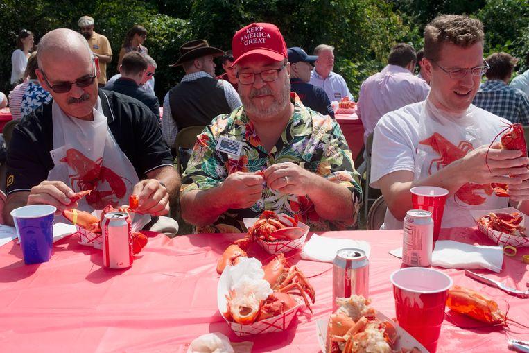 Steven Goddu (midden) met twee mede-aanhangers van Donald Trump aan de kreeft tijdens de jaarlijkse fondsenwerfactie in New Hampshire.  Beeld Ellen Kok