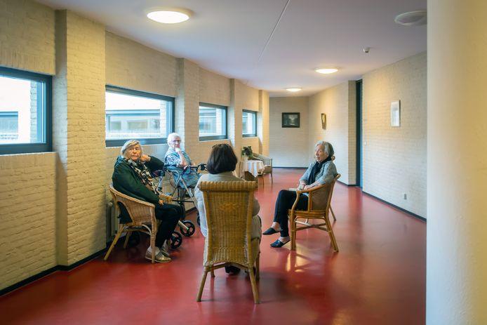Van links naar rechts: Maria van den Berg (86), de even oude Coba Ribbers en Helena Menten (78). Zelfs op deze gang zitten, mag eigenlijk niet. 'Het lijkt wel een ophokplicht voor oudjes.'