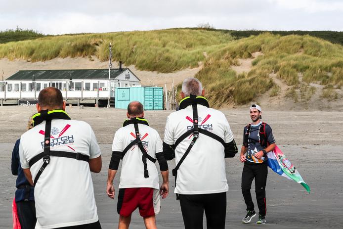 Hardloper Steven Schless uit Rotterdam en de roeiers van Dutch Marines Rowing Challenge begroeten elkaar op het strand van Westenschouwen na de eerste dag van de roeitocht Vlissingen-Rotterdam.