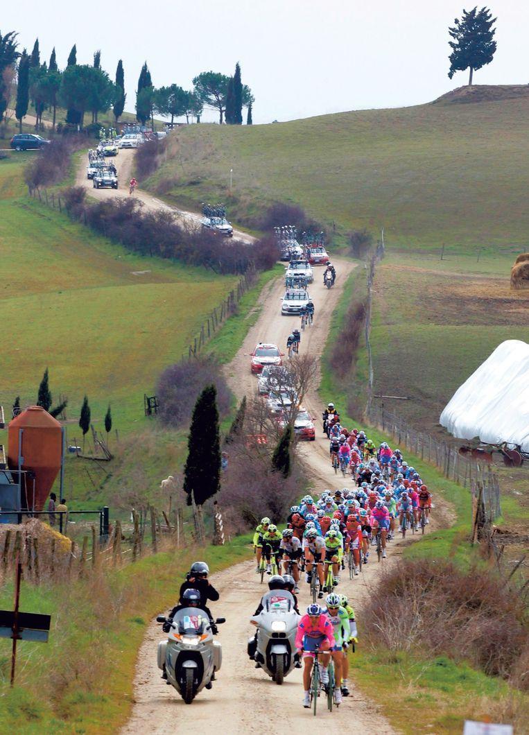 De renners razen over het grind naar beneden in de Strade Bianche van 2011. Beeld Photo News