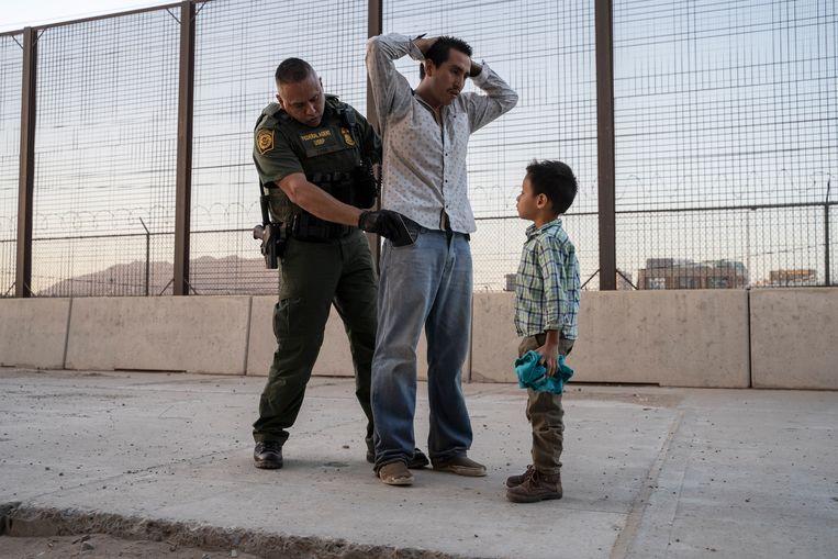 De Amerikaanse grenspolitie checkt een vader en zijn zoontje die vanuit Guatemala een maand door Mexico hebben gereisd. Beeld AFP