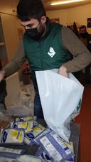 Een vrijwilliger van Abdullah Baba Foundation helpt met het samenstellen van de boodschappentassen