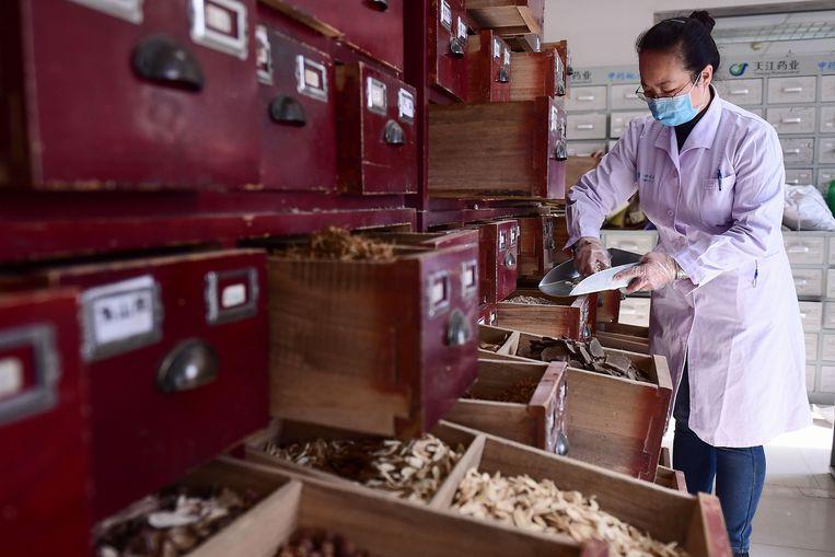 Een medewerkster van een ziekenhuis waar gewerkt wordt met traditionele Chinese medicijnen, vaak bestaande uit delen van dieren of planten.  Beeld AFP