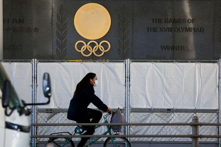Een vrouw met mondkapje passeert in Tokio het nationaal stadion van Japan, waar de openingsceremonie van de Zomerspelen moet worden gehouden.  Beeld AP