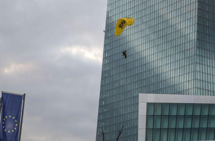 Un militant de Greenpeace atterrit avec un parapente sur le toit du siège de la Banque centrale européenne (BCE) avant de déployer une banderole contre la politique climatique de la banque, le 10 mars 2021 à Francfort-sur-le-Main, dans l'ouest de l'Allemagne.