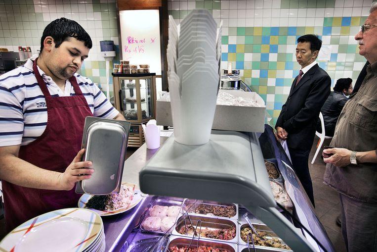 Jongeren met een Wajong-uitkering aan het werk in een broodjeszaak in de Amsterdamse Bijlmermeer. Beeld null