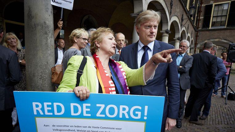 Corrie van Brenk, voorzitter van AbvaKabo biedt Martin van Rijn anderhalf jaar geleden een zorgpetitie aan tijdens een protest op het Binnenhof tegen het besluit de zorgtaken over te hevelen naar gemeenten. Inmiddels is er veel ontevredenheid over deze verandering Beeld anp
