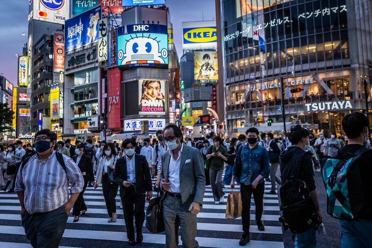 De inwoners van Tokio dragen een mondmasker op straat. De Japanse regering heeft beslist de noodtoestand, die in een deel van het land van kracht is, te verlengen tot 20 juni. Beeld Getty Images
