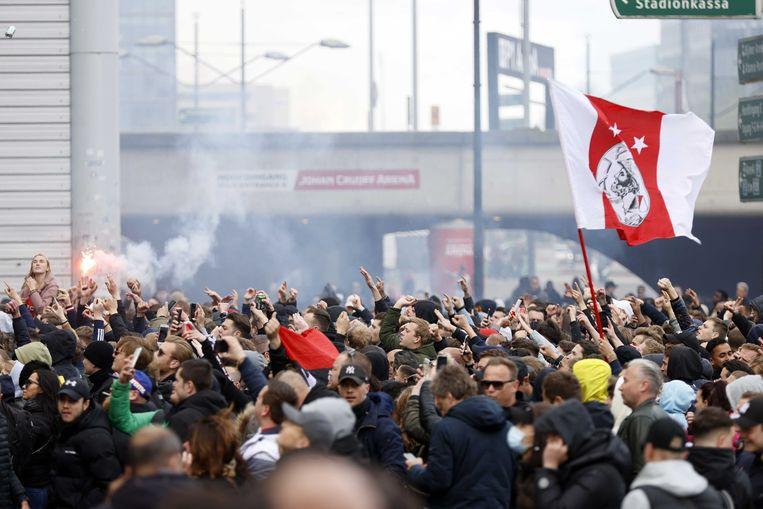 Supporters van Ajax vieren het kampioenschap  bij de Johan Cruijff Arena, waarbij alle coronaregels met voeten worden getreden.  Beeld ANP