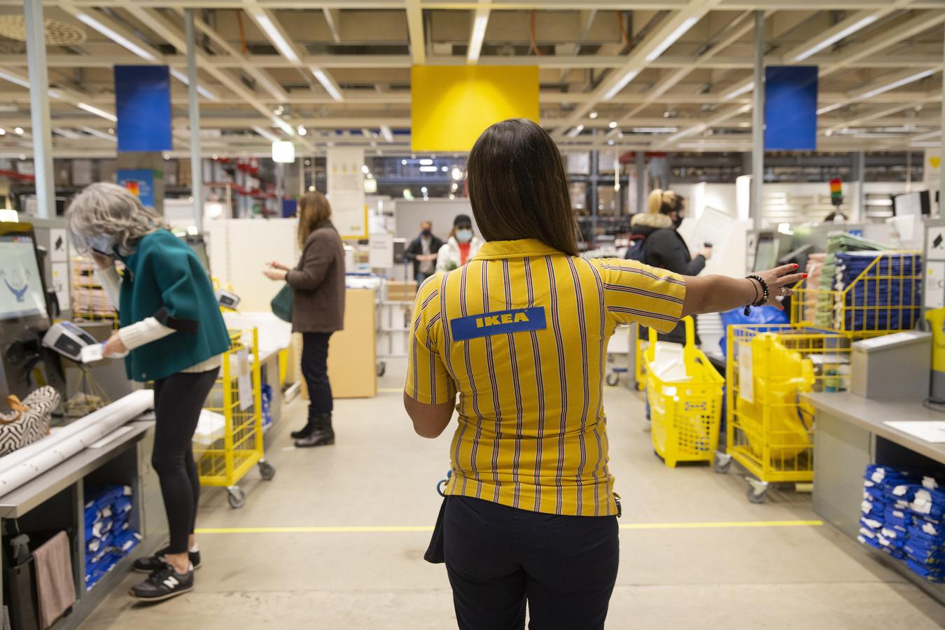 Een werknemer van Ikea wijst verschillende zelfscankassa's toe aan klanten