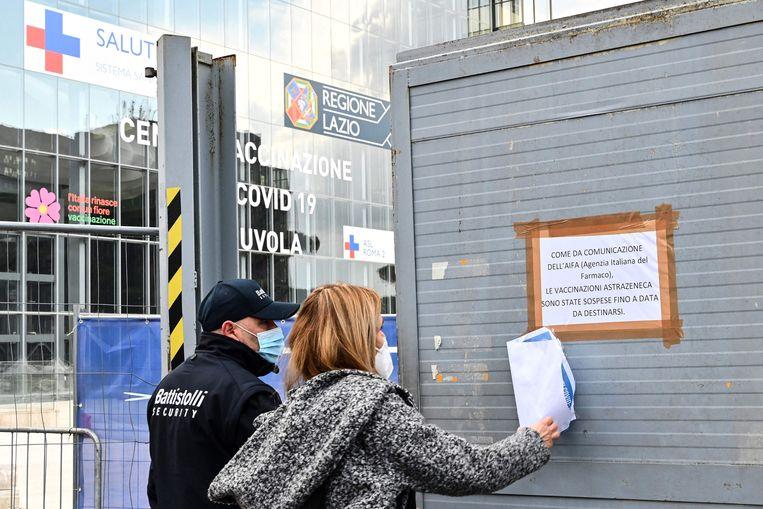 Ambtenaren van de Italiaanse regio Lazio brengen bij een vaccinatiecentrum in Rome een tekst aan waarin wordt uitgelegd dat de vaccinaties met AstraZeneca voorlopig zijn opgeschort.  Beeld AFP