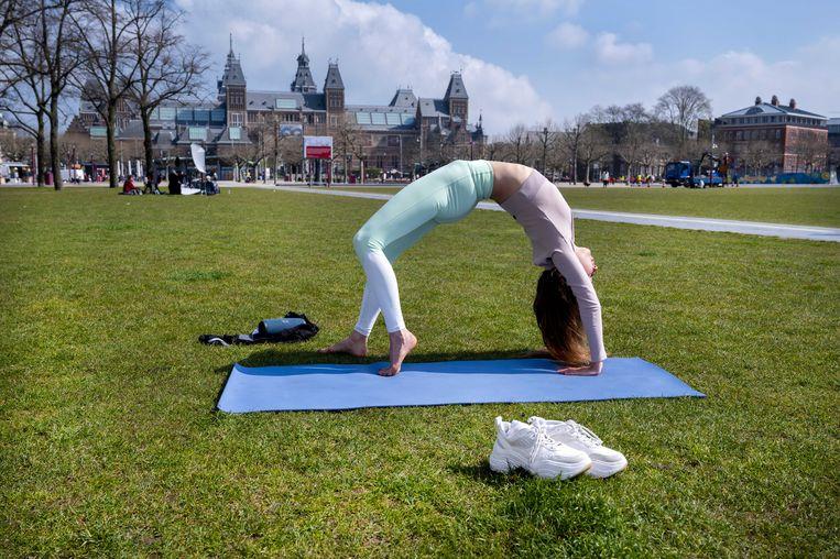 Een vrouw doet yoga-oefeningen op het Museumplein. Beeld ANP
