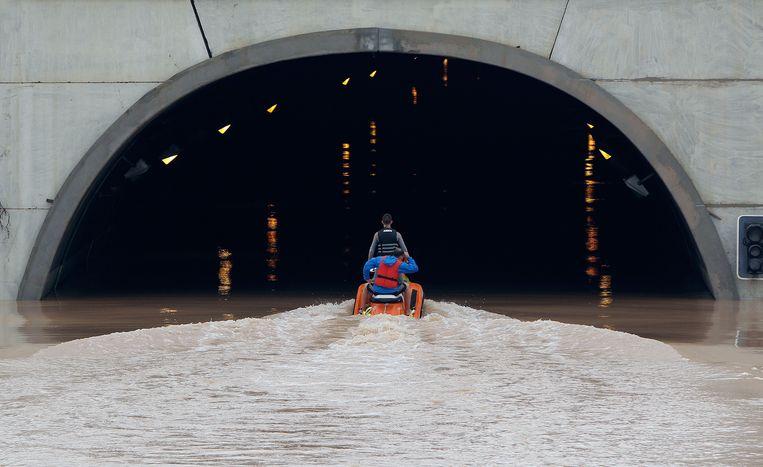 Reddingwerkers proberen mensen te redden die met hun auto vastzitten in een ondergelopen tunnel.   Beeld EPA
