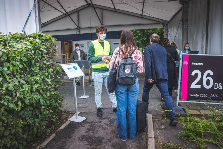 Stewards aan het testcentrum van het UZ Gent controleren of de mensen de benodigde code hebben, en helpen die te verkrijgen als dat nodig is. Beeld Wannes Nimmegeers
