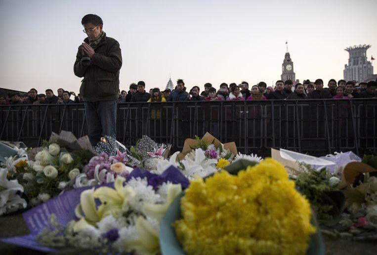 Een Chinese man bidt bij de plaats waar tientallen mensen om het leven kwamen tijdens oudejaarsnacht in Shanghai. Beeld getty