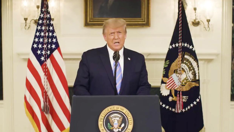 De Amerikaanse president Trump tijdens zijn videotoespraak van donderdagavond. Beeld VIA REUTERS