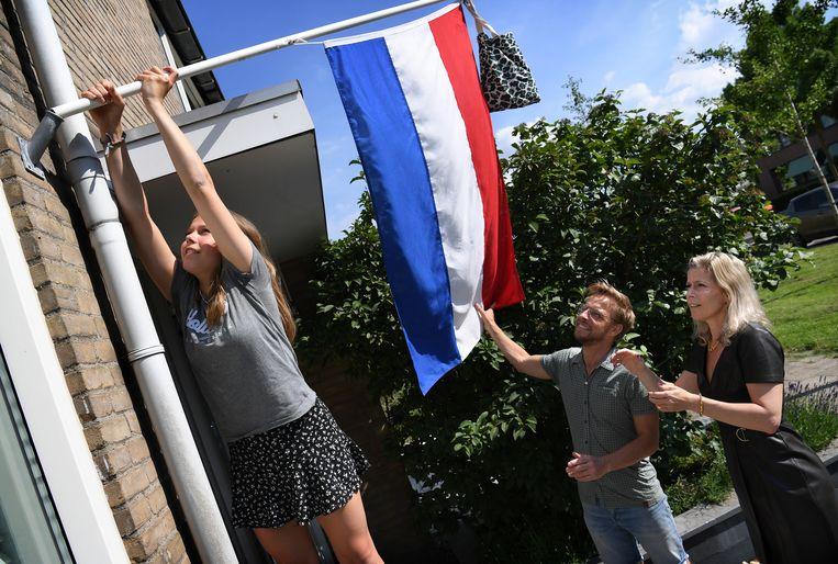 Nina uit Nieuwerkerk aan den IJssel is geslaagd voor haar vmbo-examen en hangt de vlag uit. Haar ouders kijken toe.  Beeld Marcel van den Bergh / de Volkskrant