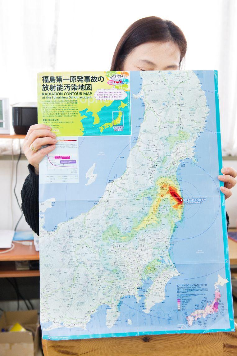 Tokiko Noguchi toont een kaart waarop het besmette gebied is aangegeven. Beeld Sanne De Wilde