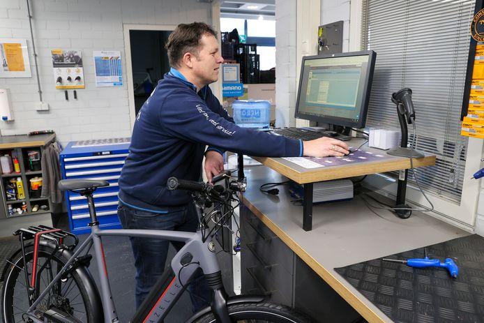 Arno van der Vegt bezig met het uitlezen van een e-bike bij Trias Fietsen in Lieshout.