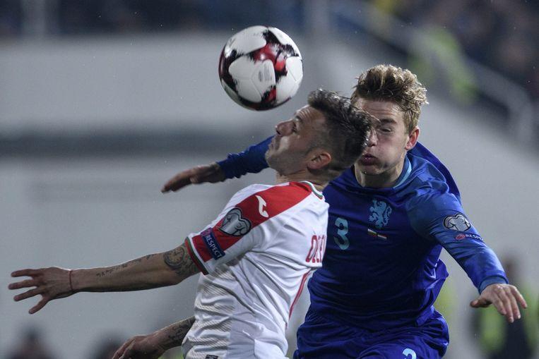 Matthijs de Ligt (R) in een kopduel met Bulgarije-speler Spas Delev in Sofia. Beeld AFP