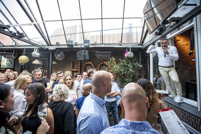 Veilingmeester Gabriël Urucoglu hangt uit het balkon van zijn horecazaak 't Hookhoes en jut de gasten op om nog wat meer te beiden op alle items.