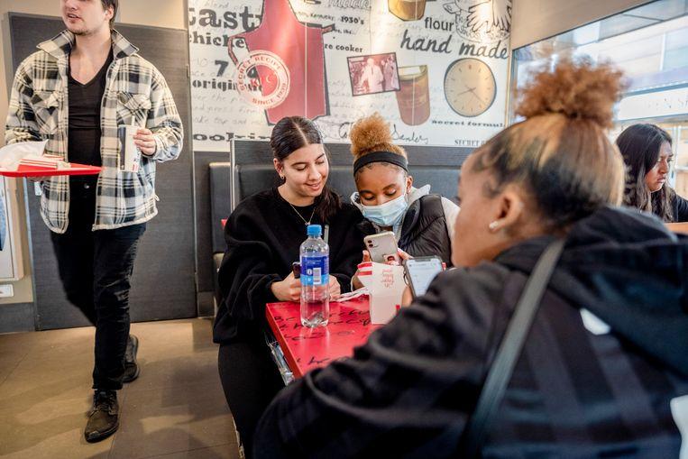 Vriendinnen Sylvia (links), Gesabel (met mondkapje) en Ndeye na schooltijd in de KFC.  Beeld Bram Petraeus