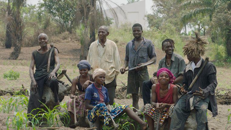 Kunstenaars en bewoners van Lusanga met op de achtergrond de White Cube.  Beeld Renzo Martens