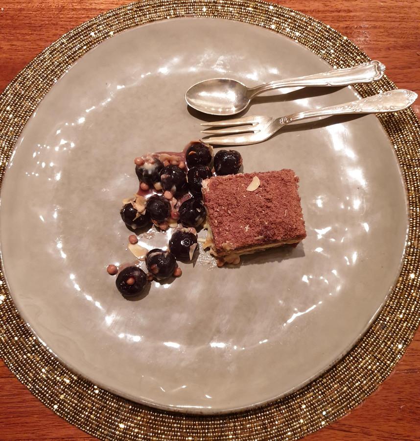 Een chocoladetaartje en taartje van amarenakers, gegarneerd met amarenakersen en crème anglaise.