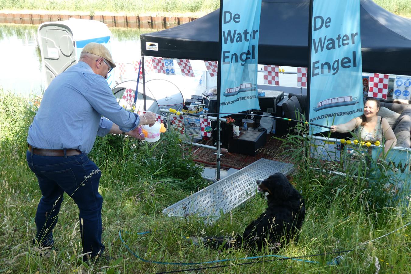 Passanten stoppen vlak bij de Dungense Brug geld in het spaarpotje dat aan een hengel is vastgemaakt voor het opknappen van de rondvaartboot De Waterengel.