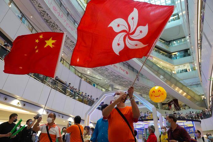 Mensen zwaaien met de Hongkongse (rechts) en de Chinese vlag (links) tijdens een kijkevenement van de Olympische Spelen in een lokaal shoppingcenter.