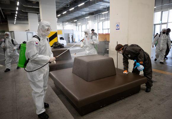 Een stelplaats voor bussen in Daegu - het epicentrum van de uitbraak in Zuid-Korea - wordt ook onder handen genomen met desinfectiemiddelen.