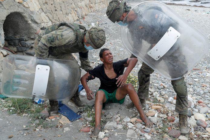 Archiefbeeld. Een Marokkaanse jongen huilt terwijl hij wordt opgetild door Spaanse soldaten nadat hij al zwemmend de Spaanse enclave Ceuta bereikte. (19/05/2021)