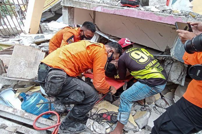 Reddingswerkers halen een overlevende van onder het puin.