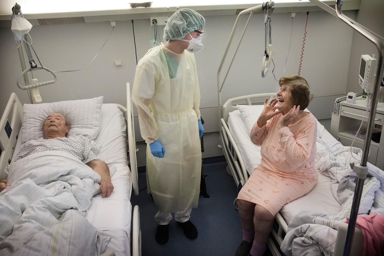 Het echtpaar Heckler, al 70 jaar getrouwd, ligt samen op de corona-afdeling van het ziekenhuis in Schöneck in de Duitse deelstaat Saksen. Zij is aan het herstellen. Beeld Daniel Rosenthal