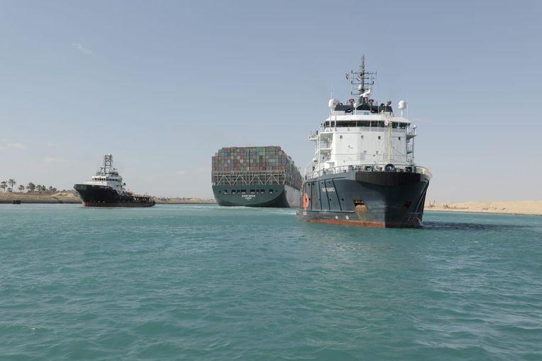 De Ever Given met de sleepboten die het schip uit de oever van het Suezkanaal hebben bevrijd.  Beeld Via Reuters