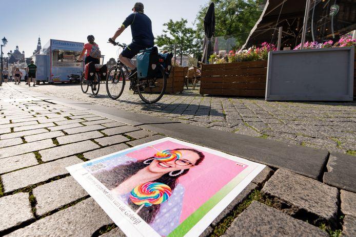 Nederland,  Den Bosch, studenten van het KW1plakken zelf ontworpen stickers op de stoeprand van de markt