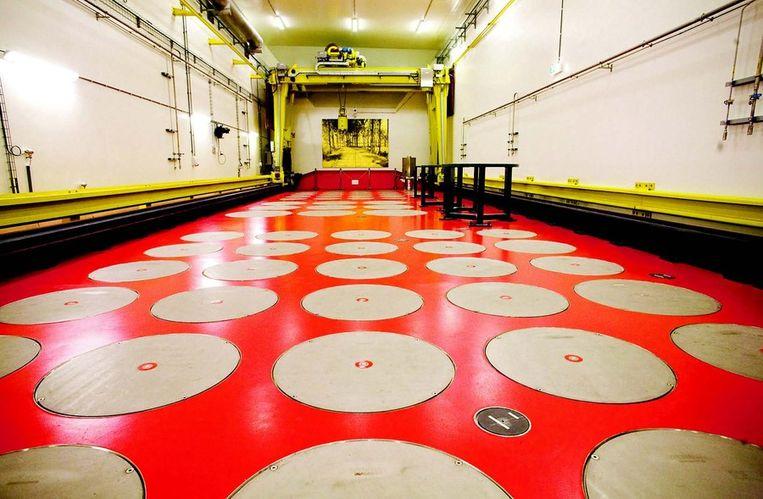 In het opslaggebouw van Covra (Centrale Organisatie voor Radioactief Afval) in het Zeeuwse Nieuwdorp ligt onder ronde metalen deksels het meeste afval van de Nederlandse kernreactoren sinds de jaren vijftig. Het blijft meer dan 200.000 jaar dodelijk en niemand heeft daarvoor de afgelopen zestig jaar een oplossing kunnen bedenken. Foto © Rob Huibers Beeld