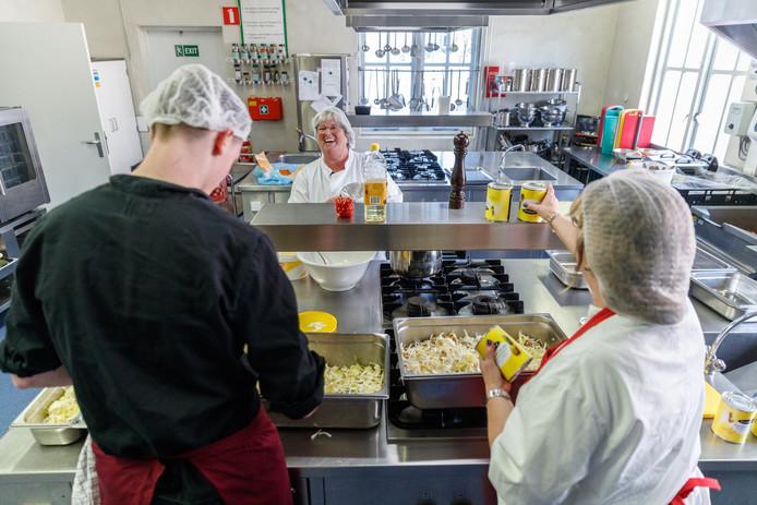 Ronald (17) mag een paar keer in de week meehelpen in de keuken van gesloten jeugdinstelling Via Almata in Ossendrecht. Medewerksters Jeanne Vriens (l.) en Yvonne van Kraanen zijn blij met de extra handjes.
